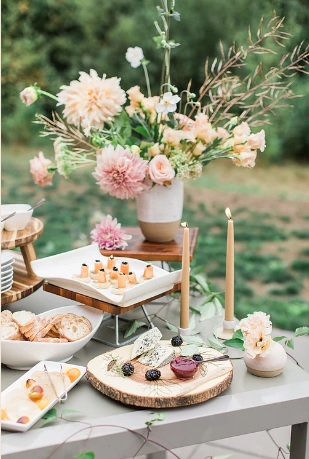 Table set with flowers, candles, and hors d'oeuvres