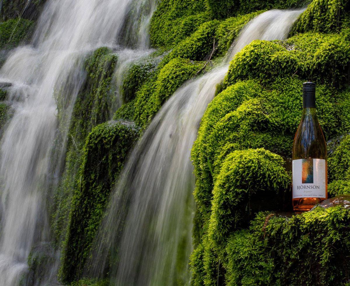 Bjornson rose bottle next to waterfalls and mossy rocks